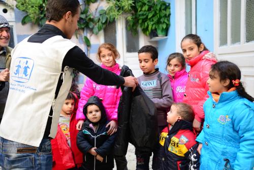 Un operatore di SOS Villaggi dei Bambini che distribuisce giacconi invernali (foto di Wissam Bachour)